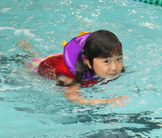 A child swims and looks at the camera