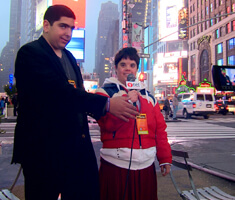 two young men with a microphone in Times Square