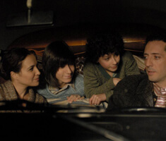 A man and woman sit in the front seat of a car, in the back seat two kids, all look at the father who is driving