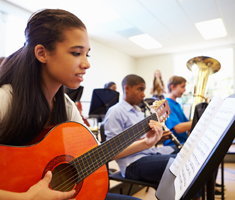 students practicing instruments in a classroom; girl in foreground practices guitar