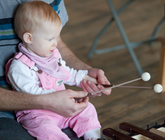 A baby sits on her caregiver's lap, he helps her hold xylophone sticks