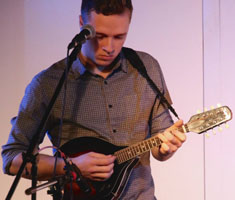 Sam Clark plays a small guitar-like instrument behind a mic