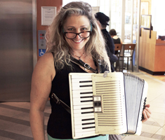 smiling woman holding an accordion