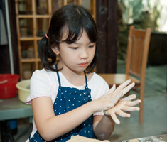 A girl rolls clay between her hands