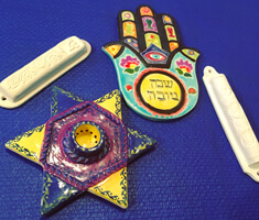 brightly painted ceramic star of david and hamsa