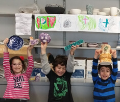 three smiling kids holding up pottery they made at the MNjcc