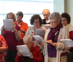 group of adults read sheet music in choir at the MNjcc