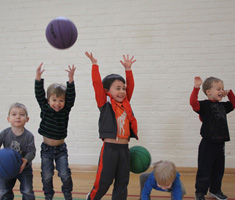 A group of children jump in the air smiling, with basketballs overhead