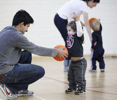 a father crouches and hands his child a basketball