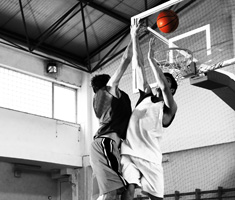 Two young men both jump for a basketball