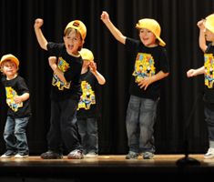 A group of children dance on a stage