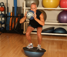 A man holds a medicine ball ready to throw