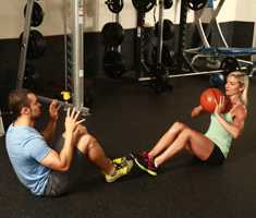 fit girl and boy sit on floor in pushup position with weighted ball.