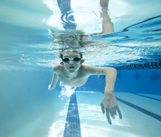 boy doing front crawl underwater in a pool, wearing goggles