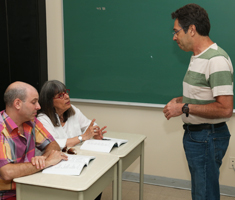 two students at desks speak with a standing teacher.