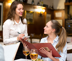 a woman holds a menu and orders from a server in a restaurant
