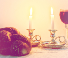 a loaf of challah, candles, and a wine glass