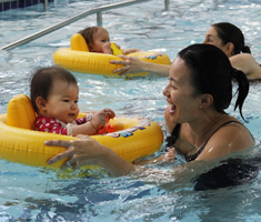 a woman in the pool with a baby floating in a yellow seat
