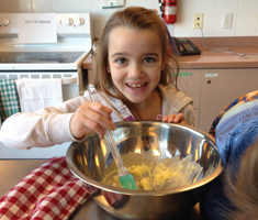 a girl mixes the contents of a bowl and smiles