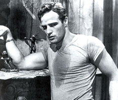 black and white film still of marlon brando leaning against a wall