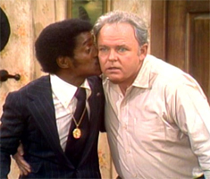A black man in a suit (Sammy Davis Jr) kisses a white man in a white shirt who looks shocked (Archie Bunker)