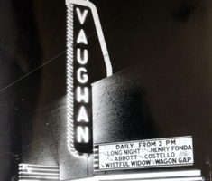 A lit up theatre marquee with a vertical sign that says VAUGHAN